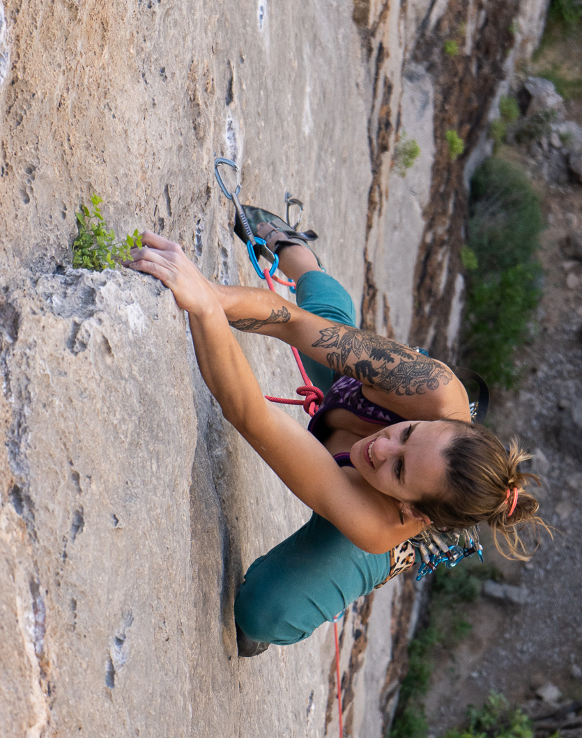 female rock climber high above the ground with tattoos